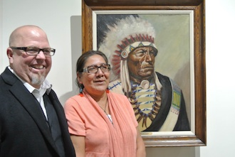 "Marian Whitemouse stands in front of the portrait of her great grandfather, Chief Iron Tail (Dewey Beard). At far left is Brent Stevens, donor of the ""Faces of Little Big Horn"" Exhibit."