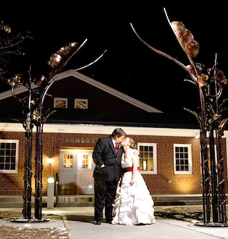 Newlyweds Matthew and Erica Temple under the portal outside the Wassenberg Art Center. The portal was designed by sculptor Michael Bendele. (Photograph by Caci Hyman of Caci Hyman Photography, Paulding.)