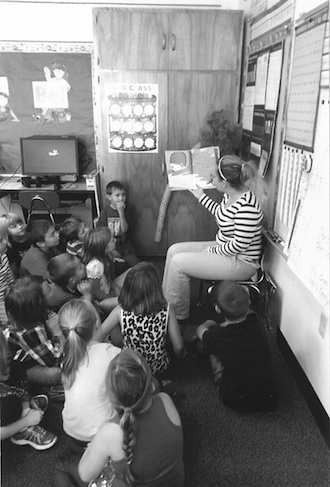 """Melissa Burk (Wright State University student) is Kristina Tow's student teacher this year. She is shown giving a lesson on recycling, reducing, and reusing based on the children's book """"The Lorax."""" (Photo submitted.)"""