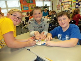 Fourth graders in Mrs. Wendel's science class learned about the rock cycle with a hands-on lesson.  From the left: Carsyn Looser, Braxton Coil, and Brendon Kesler used clay to demonstrate weathering and erosion in the rock cycle. (Photo submitted.)