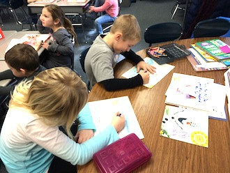 First graders Gavin Evans and Beth Hughes work on illustrations for the classroom book. (Photo submitted.)
