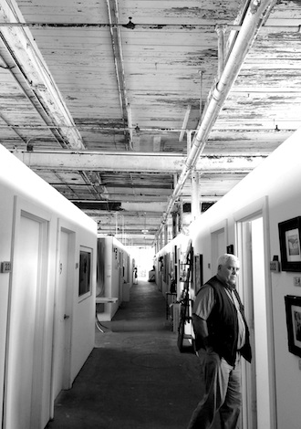 Stan Schumm inspects one painting studio among a corridor of artist studios that are now making use of the vast space in an old factory in the up-and-coming Franklinton neighborhood in Columbus.  (Photo submitted.)