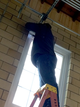 Rich Davis of John Rager Home Improvement drills through the tough ceramic blocks to install the hardware which hold floor-length drapes at the Wassenberg Art Center. (Photo submitted.)