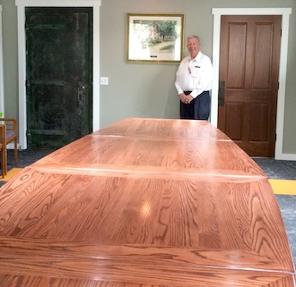 Larry Wendel stands behind the 14-foot, modular boardroom table he and his wife Gloria had specially crafted for the Wassenberg Art Center. The table was made by Dave Salway, Rockford. (Photo submitted.)
