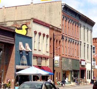 Dedicated Duck Derpy committee member Bradde Hamman painted a large, yellow duckie on the side of his downtown business Open Minded in a show of support for the upcoming rubbie duckie fundraising derby taking place at the Wassenberg Art Center on July 11. (Photo submitted.)