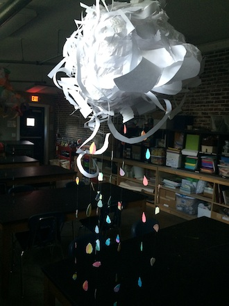 Rainbow colored drops emerge from storm clouds created by Wassenberg Art Center camp students earlier this summer.  (Photo submitted.)