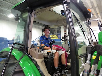 Jacob, a Lincolnview 8th grader, gets comfortable in a new tractor in the Ag & Industrial Power Technology lab. (Photo submitted.)
