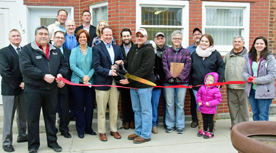Scott Hawken of Apex Clean Energy cuts the ribbon on the company's development office in Ohio City, while Van Wert Area Chamber of Commerce officials and village residents look on. (Dave Mosier/Van Wert independent)