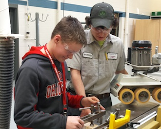 Kollan Dull, a Lincolnview sophomore, listens carefully as Vantage senior Carpentry student Brad Rice (Ft. Jennings) explains how to operate the shaper. (Photo submitted.)