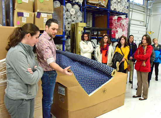 Sticky Rammel, national sales manager for KAM Manufacturing, shows Lincolnview teachers some of the fabric used in the company's Stephanie Dawn line of purses. (Dave Mosier/Van Wert independent)