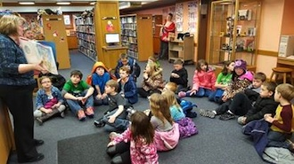 On Feb. 22 the Lancer Learning Academy took a field trip to the Brumback Library. At the library, students were given a tour of the different areas and told about its history. Students are shown listening to Marsha Weldy read a story about George Washington's teeth. (Photo submitted.)