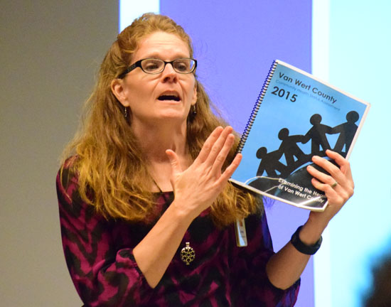 Van Wert County Hospital staff member Anne Dunn holds up a copy of the 2015 Van Wert County Community Health Assessment during a presentation on Wednesday. (Dave Mosier/Van Wert independent)