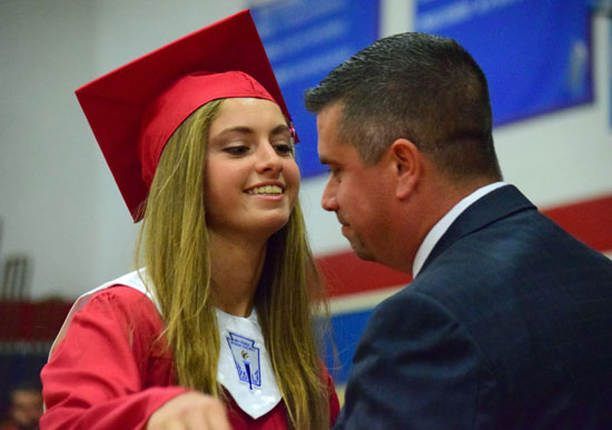 Crestview Local Board of Education member Wes Skelton shares a moment with his daughter, Leslie, after presenting her with her diploma. (Dave Mosier/Van Wert independent)