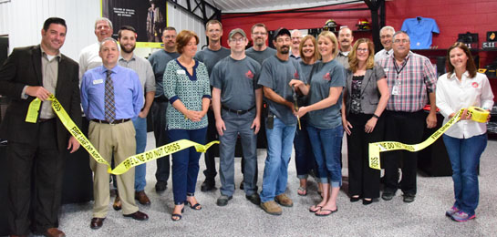 Jenni and Brandon Bowen cut the ribbon on their renovated showroom while Van Wert Area Chamber of Commerce board members and company employees look on. (Dave Mosier/Van Wert independent)