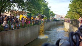 Crowds line the creek as a front end loader operated by the Van Wert County Engineer Department dumps over 500 pounds of racing rubber duckies in Town Creek during the First Annual Town Creek Live. (Photo caption.)