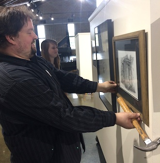 Office Manager Matt Temple and other Wassenberg Art Center staff are busy hanging artwork for the opening of the 60th Annual June Art Exhibit. (Photo submitted.)