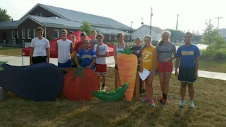 Members of the Lincolnview Cross Country Team stopped by for a photo op with giant veggies at the Wassenberg Art Center during 4-Fridays Farm Market.   (Photo submitted.)
