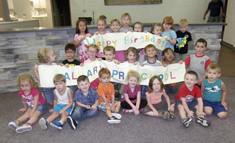 Calvary Preschool students hold up banners celebrating the Preschool's 50th anniversary. (photo submitted)