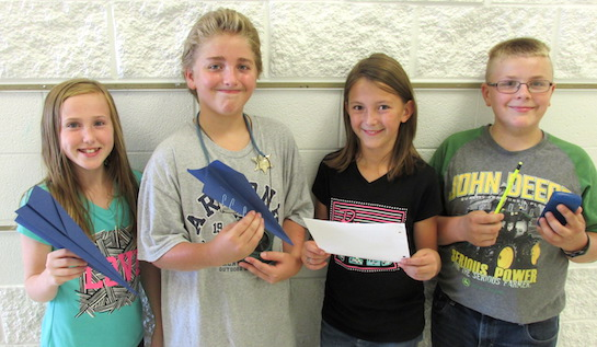 Fifth graders at Lincolnview Elementary recently learned more about the scientific method by designing and conducting investigations with paper airplanes.  Each group formed their own testable hypothesis and later shared their results with their classmates.  (Photo submitted.)