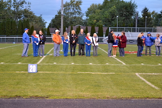 A few of the seniors with their parents are lined up during the ceremony at the football game last Friday night. (Photo submitted.)