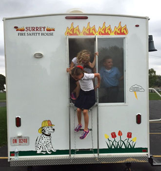 Local students exit the smoke-filled Fire Safety House this week. (photo submitted)