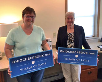 Latta Fiscal Officer Kay Miller and Scott Fiscal Officer Hilary Yoder with signs noting their villages' participation in the Ohio Checkbook.com project. (photo submitted)