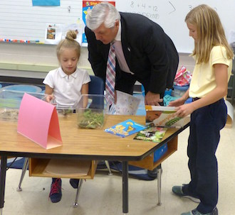 First grade student Mrkynlee Dickinson shares information about the Wooly Bear Caterpillar with Van Wert Mayor Jerry Mazur and fourth grade student Braelynn Burk. (Photo submitted,)