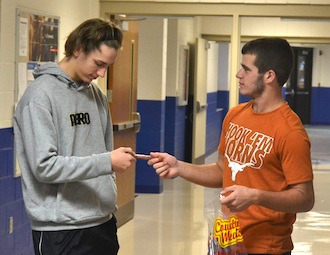 Crestview senior FFA member Chase Clark sells a beef stick to senior Lance Camp as part of the FFA traditional fundraiser. (Photo submitted.)