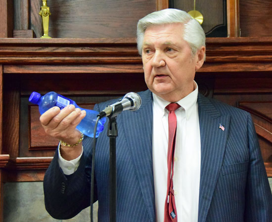 Van Wert Mayor Jerry Mazur holds up a bottle of water, the cost of which he said would equal what a city resident making $50,000 would pay a week in additional income taxes Dave Mosier/Van Wert independent