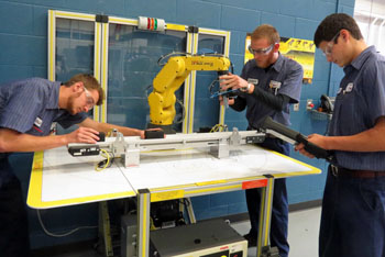 Vantage juniors Clay Schnipke (Ottoville), Robert Germann (Crestview), and Tyler Brecht (Continental) work as a team on the Fanuc automated material handling robot in the Industrial Mechanics lab.  Come to Open House on Monday, February 27, from 5-7:30 p.m., to see more demonstrations in all 18 career technical education labs. (Vantage photo)