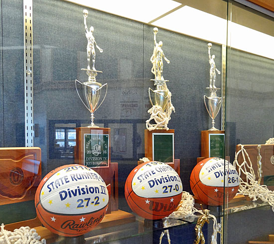 The 196-97 Lancer boys' basketball team's state championship trophy is flanked by state runner-up trophies earned in 1996 and 2016 in the Lincolnview High School trophy case. Scott Truxell/Van Wert independent
