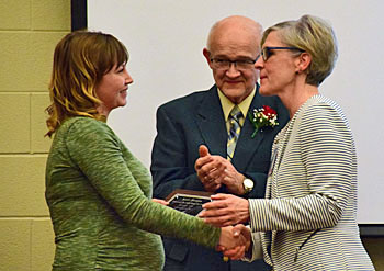 Hall of Fame inductee Kent Taylor's daughter, Sarah Perrott (left) accepts his Hall of Fame plaque from Vantage Superintendent Staci Kaufman, while former Vantage high school director Bob Brinkman looks on.