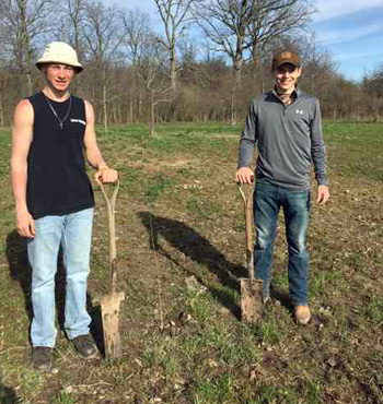Chayten Overholt and Jaden Youtsey help create a pollinator plot. (photo submitted)